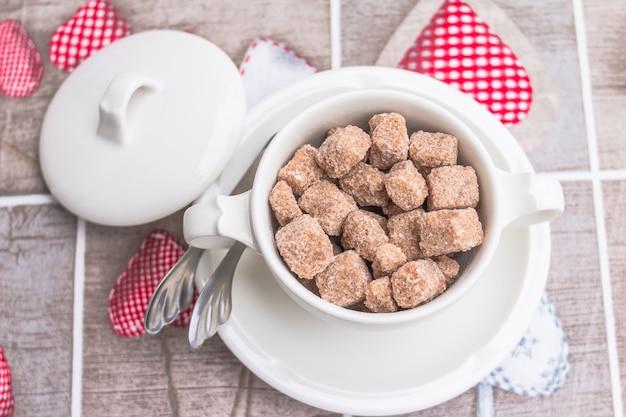 Brauner zuckerrohrwürfel in der weißen schüssel mit tafelsilber auf tabelle Premium Fotos