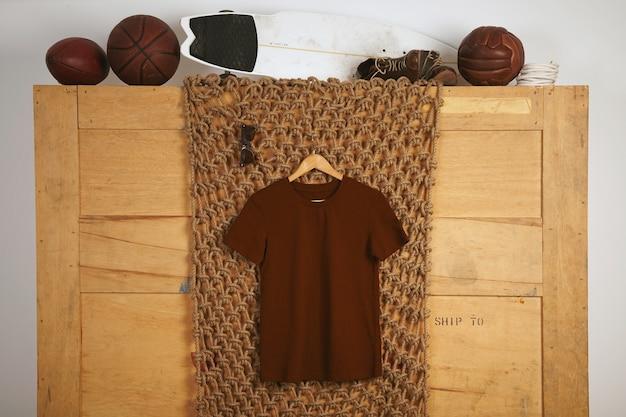 Braunes basic-baumwoll-t-shirt im rustikalen interieur mit vintage-lederspielbällen Kostenlose Fotos