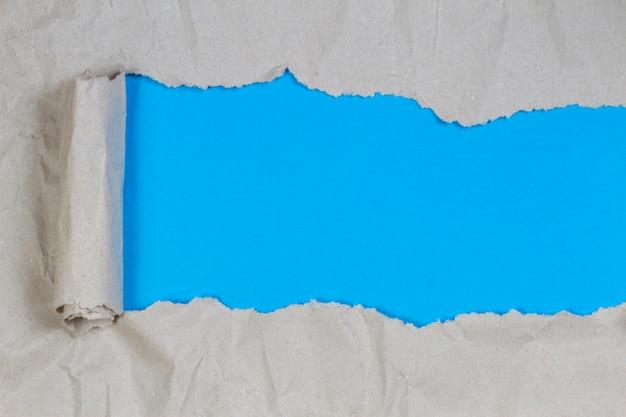 Braunes paketpapier zerrissen, um hellblauen hintergrund zu enthüllen Premium Fotos