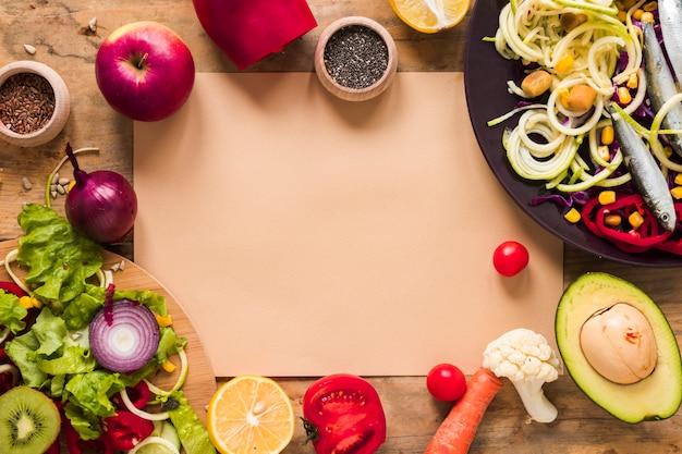 Braunes papier, umgeben von gesundem gehacktem gemüse; früchte; zutaten auf dem tisch Kostenlose Fotos