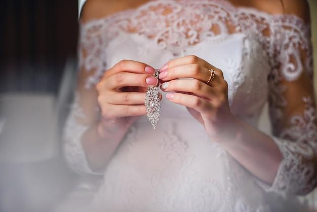 Braut, die brautohrringe in den händen auf weißem kleiderhintergrund hält Premium Fotos