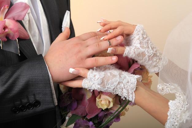 Braut, die ehering auf den finger des bräutigams legt Premium Fotos