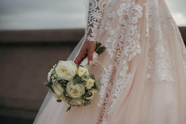 Braut, die ein schönes hochzeitskleid trägt und den blumenstrauß ihres hochzeitstags der schönen rosen hält Kostenlose Fotos