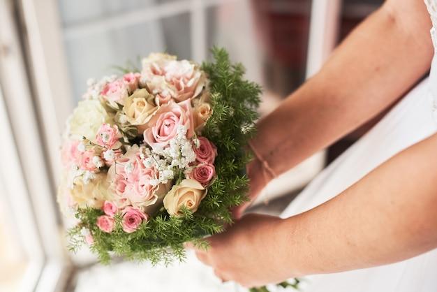 Braut, die einen blumenstrauß von rosa rosen in einer rustikalen art hält. Premium Fotos