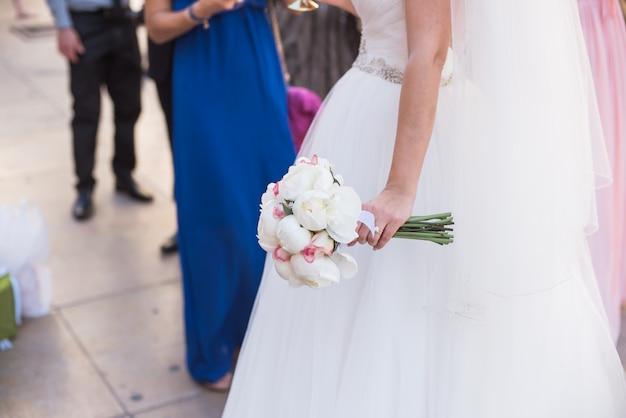 Braut, die einen blumenstrauß von weißen blumen in einer rustikalen art hält Premium Fotos