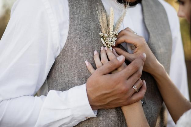 Braut, die einen boutonniere auf die stilvolle bräutigamweste setzt Kostenlose Fotos