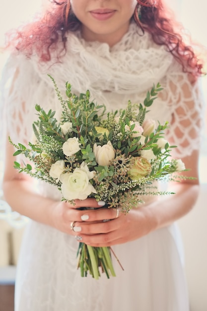 Braut, die einen hellen hochzeitsblumenstrauß mit verschiedenen blumen hält Premium Fotos