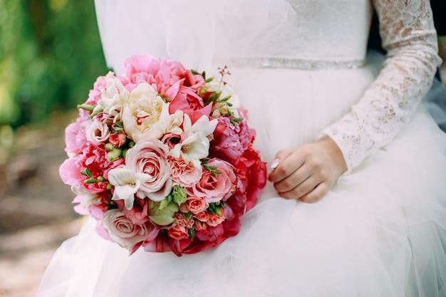 Braut, die frühlingsblumenstrauß mit rosa flowres hält Premium Fotos