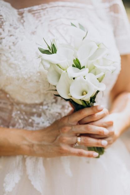 Braut, die ihren blumenstrauß an ihrem hochzeitstag hält Kostenlose Fotos