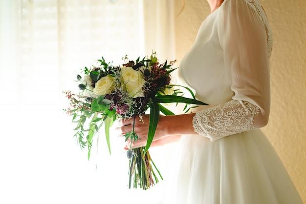 Braut, die ihren hochzeitsblumenstrauß anhält Premium Fotos
