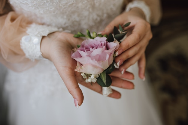 Braut hält eine butonholle mit rosa rose Kostenlose Fotos