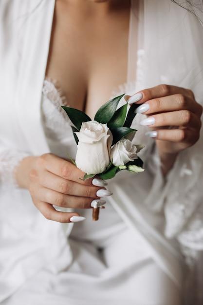 Braut hält eine butonholle mit rosen Kostenlose Fotos
