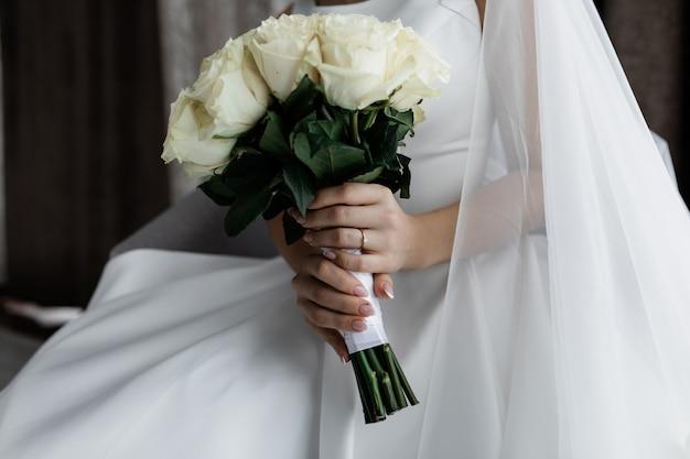 Braut hält noblen blumenstrauß der weißen rose in ihren händen Kostenlose Fotos