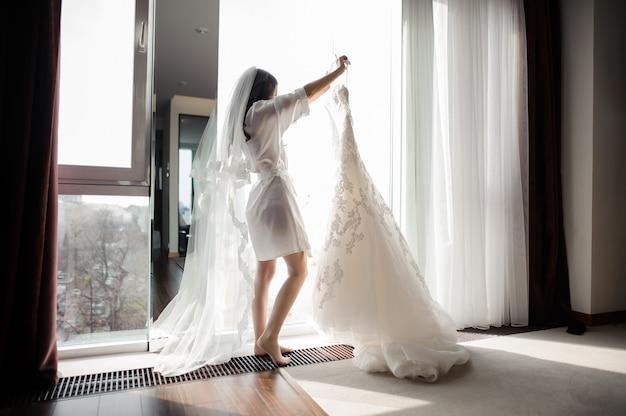 Braut im hausmantel und schleier, die hochzeitskleid auf einem aufhänger halten Premium Fotos
