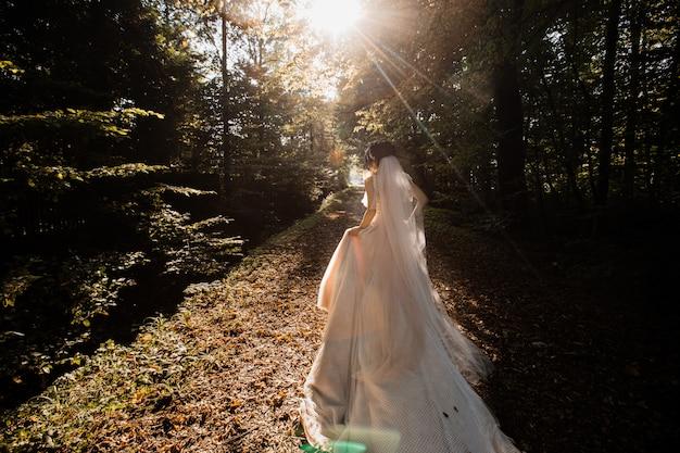 Braut im langen hochzeitskleid geht auf den waldweg Kostenlose Fotos