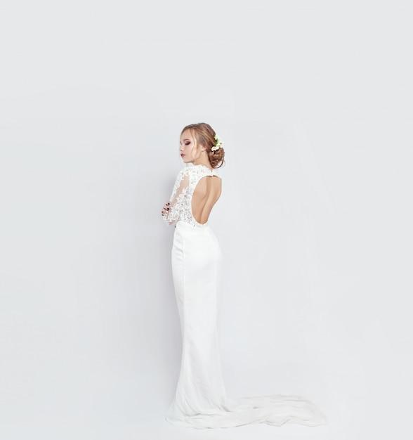 Braut im langen weißen hochzeitskleid auf einem weiß Premium Fotos
