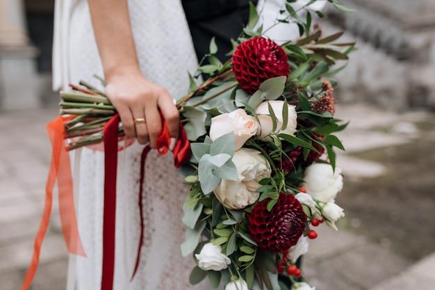 Braut im weißen kleid hält ein reiches bouquet von roten und weißen blüten Kostenlose Fotos