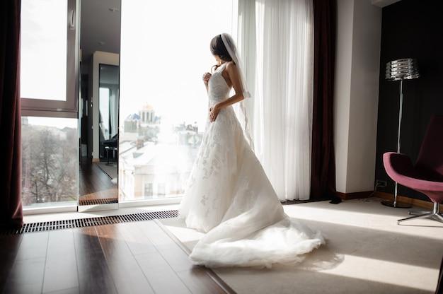 Braut im weißen spitzen- hochzeitskleid und im schleier, die durch das fenster schaut Premium Fotos