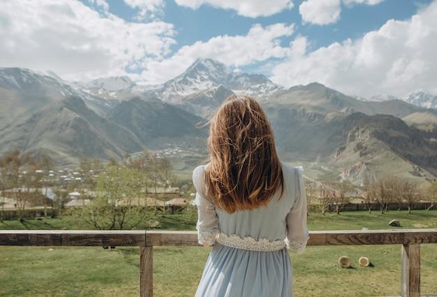 Braut in einem kleid, das auf den bräutigam schaut die berge mit schneespitzen wartet Kostenlose Fotos