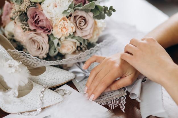 Braut legt ihre hände auf den tisch nahe blumenstrauß, schuhen und anderen brautdetails Kostenlose Fotos
