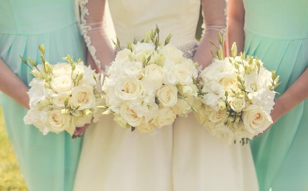 Braut mit brautjungfern, die hochzeitssträuße halten Kostenlose Fotos