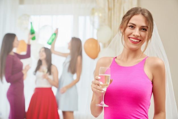 Braut mit champagner sitzt auf junggesellenabschied. Premium Fotos