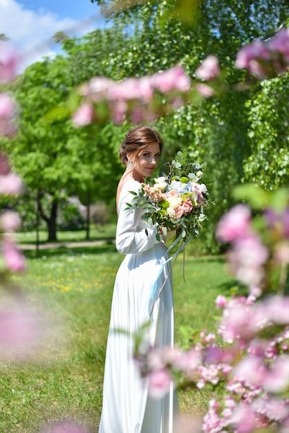 Braut mit einem blumenstrauß im sommerpark Premium Fotos