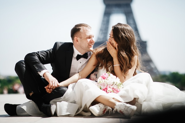 Braut sitzt in snickers vor dem eiffelturm in paris, während bräutigam ihre hand hält Kostenlose Fotos