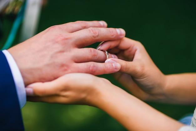 Braut trägt den ring auf dem finger des bräutigams bei der hochzeitszeremonie Premium Fotos