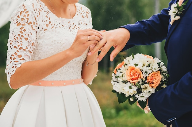 Braut trägt einen ring am finger des bräutigams bei der hochzeit Premium Fotos