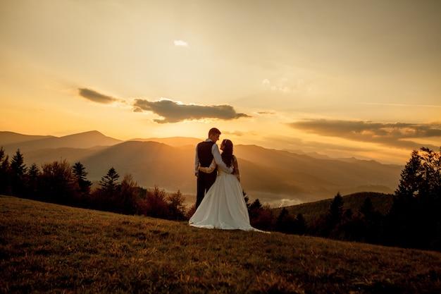 Braut und bräutigam am sonnenuntergang-romantischen verheirateten paar Premium Fotos