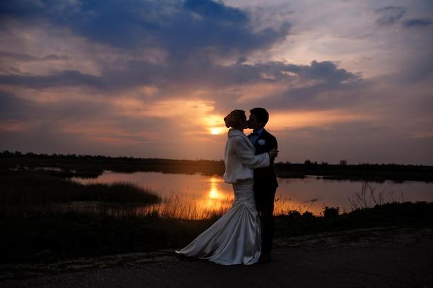 Braut und bräutigam, die am schönen romantischen verheirateten paar des sonnenuntergangs küssen Premium Fotos