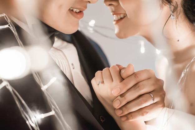 Braut und bräutigam, die hand im feenhaften licht halten Premium Fotos