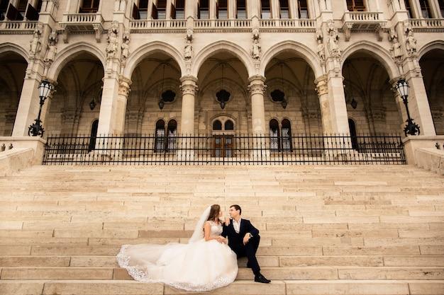 Braut und bräutigam, die in der alten stadtstraße umarmen. hochzeitspaar geht in budapest nahe parlamentsgebäude. Premium Fotos