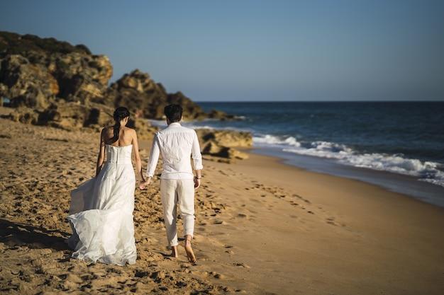 Braut und bräutigam gehen am sandstrand spazieren Kostenlose Fotos
