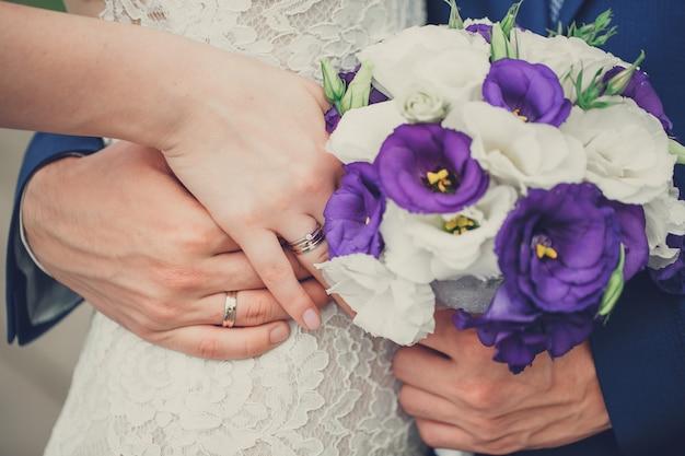 Braut und bräutigam halten ihre hände mit ringen über einem hochzeitsblumenstrauß mit den blauen und weißen blumen Premium Fotos