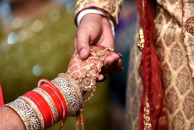 Braut und bräutigam hand zusammen in der indischen hochzeit Premium Fotos