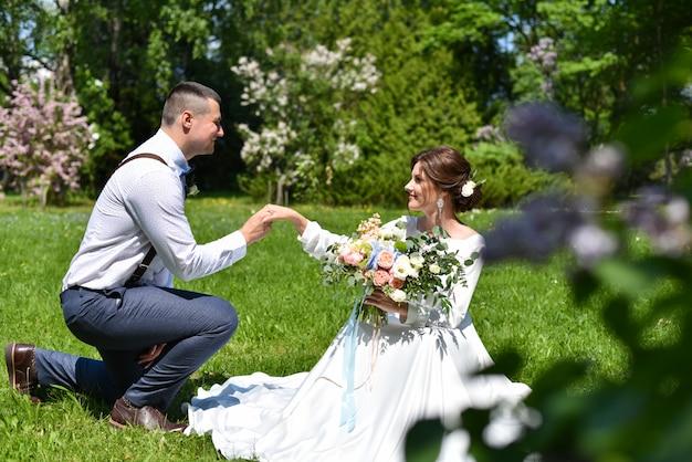 Braut und bräutigam in einem blumenstrauß gehen in einen grünen park Premium Fotos