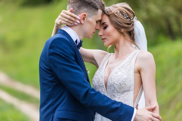 Braut und bräutigam in einem park küssen. paar brautpaar und brautpaar bei einer hochzeit im grünen wald der natur küssen fotoporträt. brautpaar Premium Fotos
