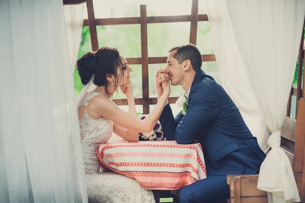 Braut und bräutigam mit dem hochzeitsblumenstrauß, der am tisch in einem café auf der sommerterrasse sitzt Premium Fotos