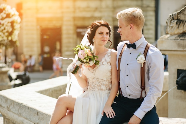 Braut und bräutigam posieren am alten brunnen Kostenlose Fotos