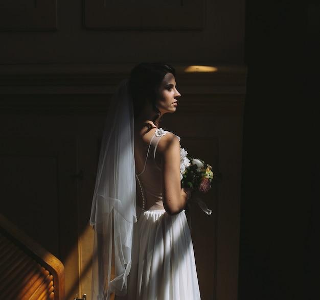 Braut und bräutigam posieren in dem schwach beleuchteten raum Kostenlose Fotos