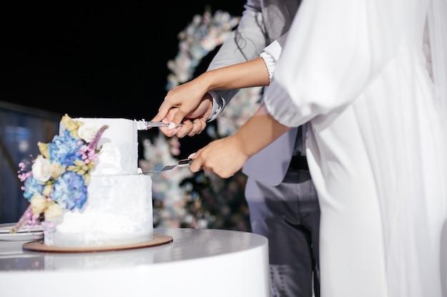 Braut und bräutigam schneiden die hochzeitstorte Premium Fotos