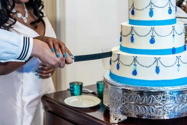 Braut und bräutigam schneiden die schöne weiße hochzeitstorte - interracial ehekonzept Kostenlose Fotos