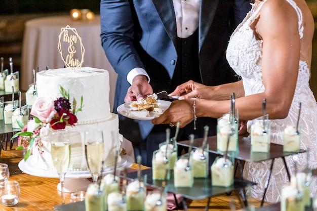Braut und bräutigam schneiden die schöne weiße hochzeitstorte Kostenlose Fotos