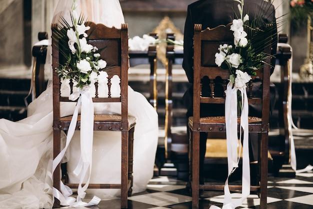Braut und bräutigam sitzen auf stühlen an ihrem hochzeitstag, von hinten Kostenlose Fotos