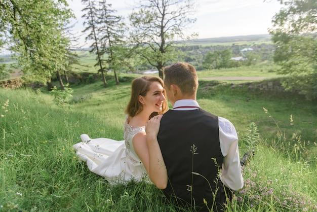 Braut und bräutigam sitzen im grünen gras. Premium Fotos