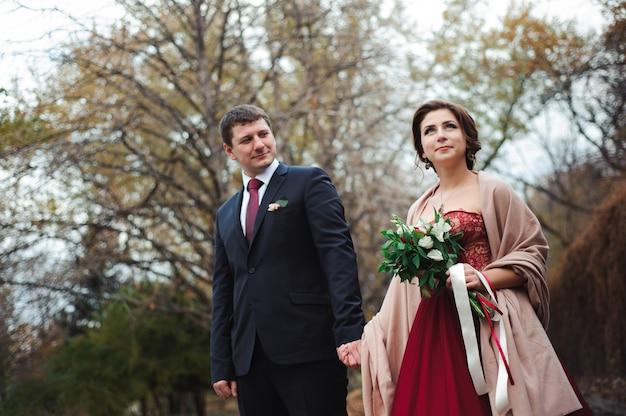 Braut und bräutigam umarmen in einem wald im herbstwald, hochzeitsspaziergang Premium Fotos