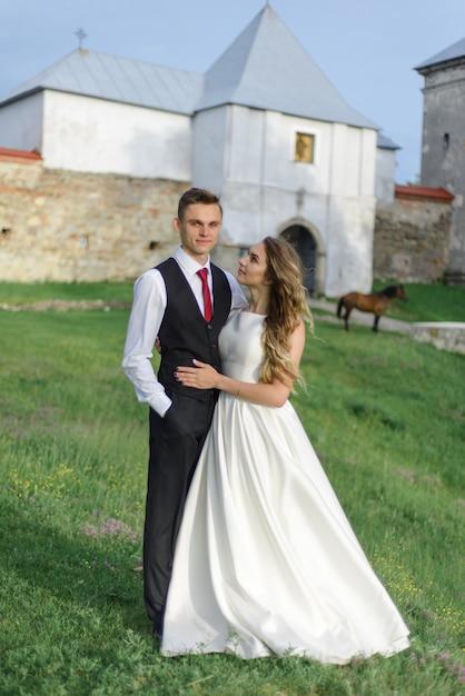 Braut und bräutigam umarmen sich vor dem hintergrund des alten klosters. Premium Fotos