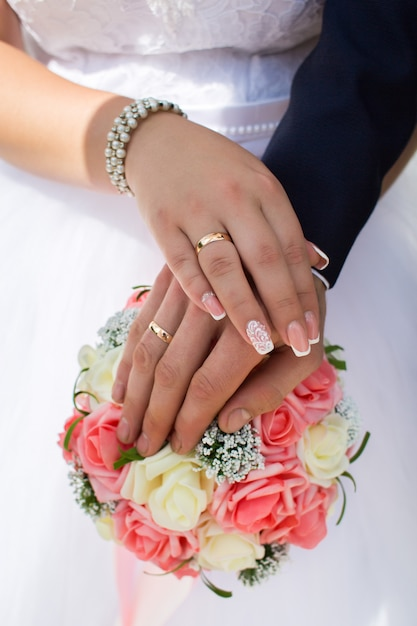 Braut und bräutigam zeigen ihre eheringe auf dem hintergrund des straußes Premium Fotos